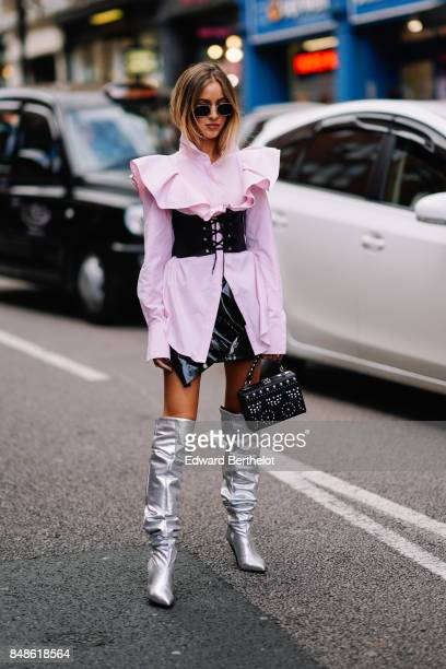 Guest wears a pink ruffled top, a black large belt, silver thigh high boots, a black skirt, a black bag, outside Topshop, during London Fashion Week...