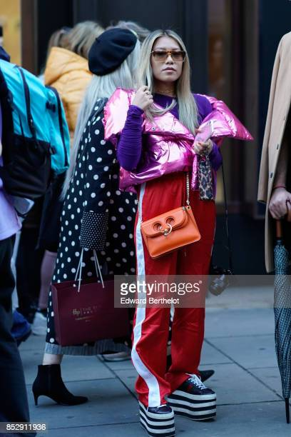 A guest wears a pink shiny puffer coat a purple pull over an orange bag oversized red striped sportswear pants platform shoes sunglasses during...