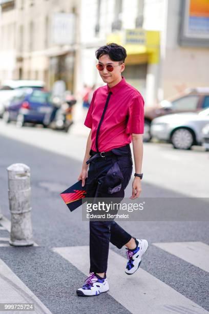 A guest wears a pink shirt a black tie a belt black pants sneakers outside Wooyoungmi during Paris Fashion Week Menswear SpringSummer 2019 on June 23...