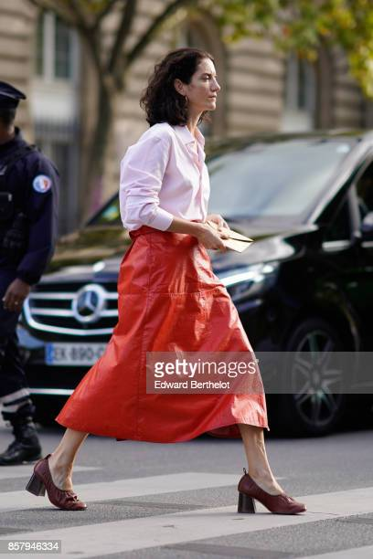 A guest wears a pink shirt a red leather skirt red shoes outside Thom Browne during Paris Fashion Week Womenswear Spring/Summer 2018 on October 3...