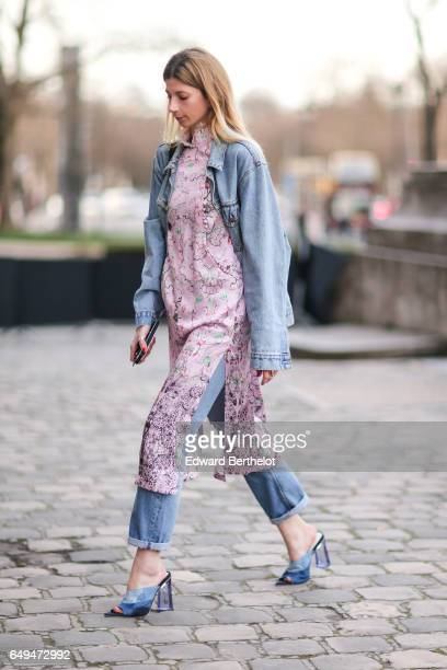 A guest wears a pink silk dress with flower print a blue denim jacket blue jeans and blue heels outside the Shiatzy Chen show during Paris Fashion...