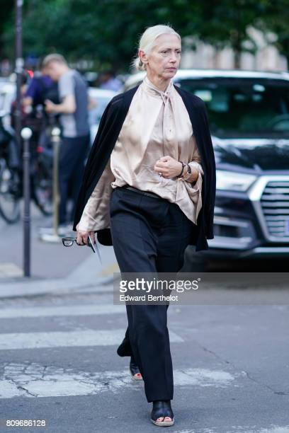 A guest wears a pink silk shirt black pants black shoes outside the Fendi during Paris Fashion Week Haute Couture Fall/Winter 20172018 on July 5 2017...