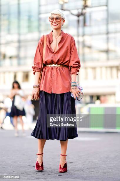 A guest wears a pink silk top a golden belt a dark blue pleated skirt red shoes a red bag sunglasses outside Fendi during Paris Fashion Week Haute...