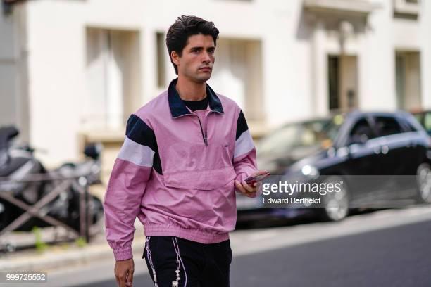 A guest wears a pink sportswear jacket outside Wooyoungmi during Paris Fashion Week Menswear SpringSummer 2019 on June 23 2018 in Paris France