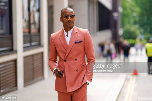 A guest wears a pink suit and blazer jacket during London Fashion Week Men's June 2018 on June 09 2018 in London England