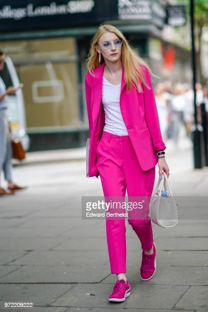 A guest wears a pink suit pink blazer jacket pink pants sneakers a white tshirt during London Fashion Week Men's June 2018 on June 09 2018 in London...