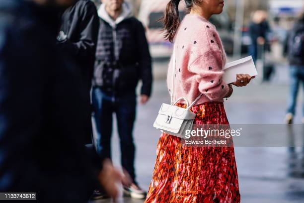 Guest wears a pink top, a white bag, a red floral print pleated skirt, outside Giambattista Valli, during Paris Fashion Week Womenswear Fall/Winter...