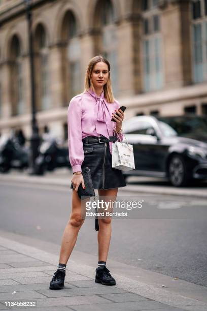A guest wears a pink top with a bow black leather skirt a black alligator pattern wristlet bag black Chanel sneakers outside Paul Joe during Paris...