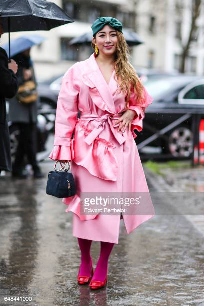 A guest wears a pink trench coat outside the Celine show during Paris Fashion Week Womenswear Fall/Winter 2017/2018 on March 5 2017 in Paris France