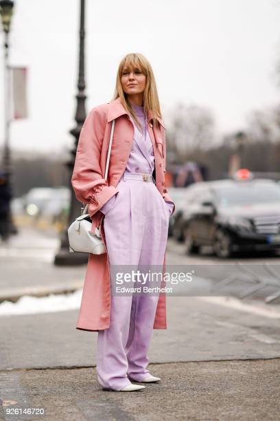 A guest wears a pink trench coat purple pants during Paris Fashion Week Womenswear Fall/Winter 2018/2019 on March 1 2018 in Paris France