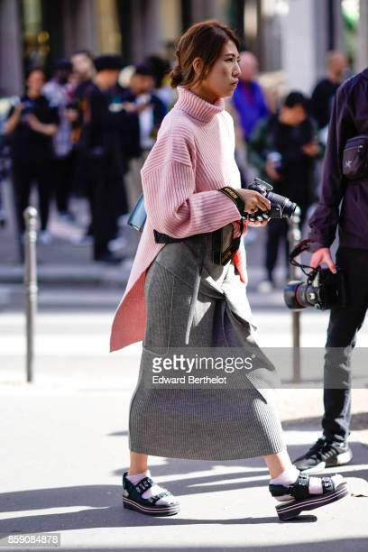A guest wears a pink turtleneck top gray skirt sandals white socks outside Acne Studios during Paris Fashion Week Womenswear Spring/Summer 2018 on...