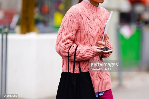 A guest wears a pink wool pullover outside Chanel during Paris Fashion Week Womenswear Spring/Summer 2019 on October 2 2018 in Paris France