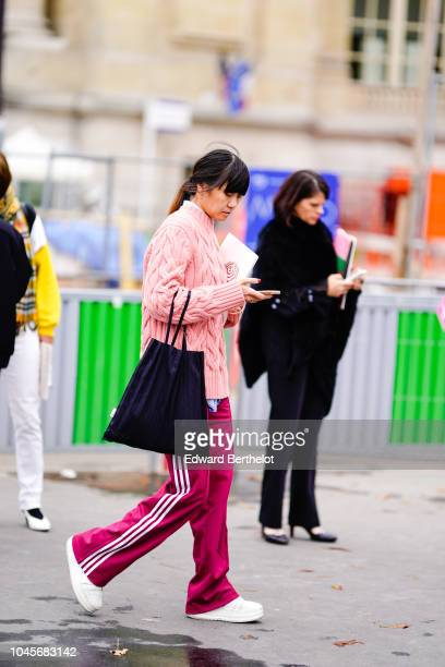 A guest wears a pink wool pullover purple striped sportswear pants white sneakers shoes outside Chanel during Paris Fashion Week Womenswear...