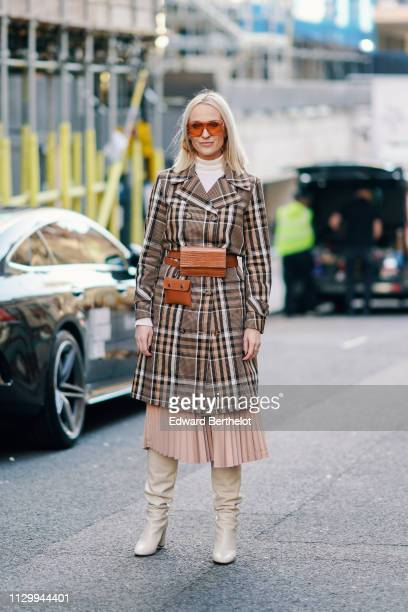 A guest wears a plaid checked coat a brown belt leather bag pink pleated skirt white boots during London Fashion Week February 2019 on February 15...