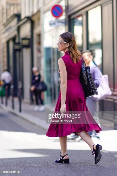 A guest wears a pleated purple dress black shoes outside Thom Browne during Paris Fashion Week Menswear SpringSummer 2019 on June 23 2018 in Paris...