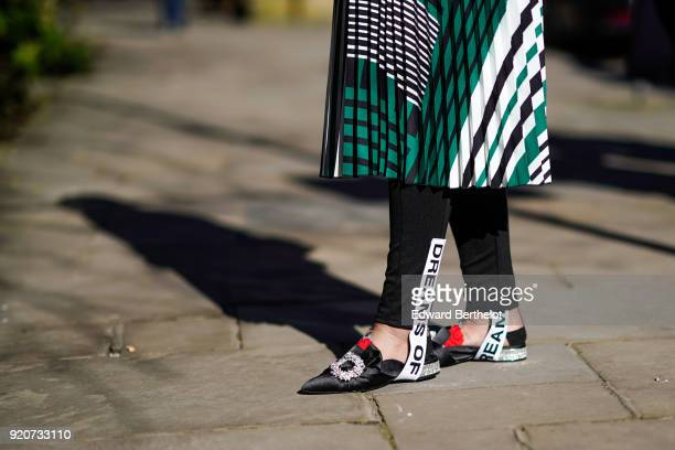 A guest wears a pleated skirt black leggings black shoes during London Fashion Week February 2018 on February 17 2018 in London England