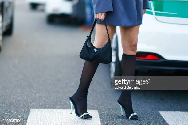A guest wears a Prada bag tights green shoes outside Prada during Milan Fashion Week Menswear Fall/Winter 2020/2021 on January 12 2020 in Milan Italy