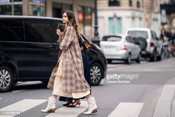 A guest wears a Prince of Wales check trench coat a beige floral print fringed scarf beige cowboy boots outside Paul Joe during Paris Fashion Week...