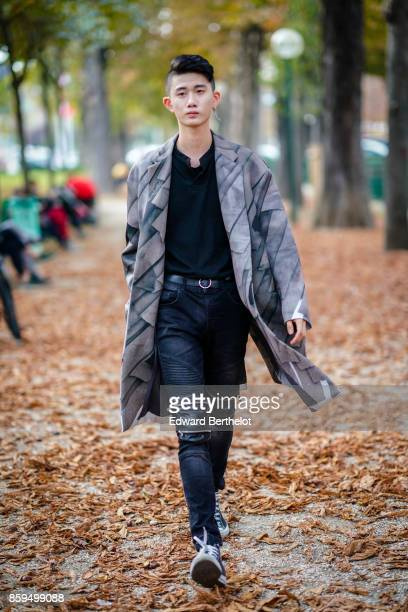 A guest wears a print grey coat a black top blue navy denim pants with zipped kneepads a black belt navy blue sneakers outside the Rochas show during...