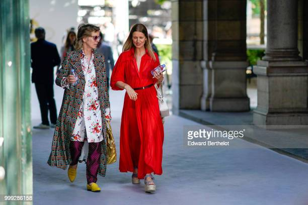A guest wears a printed geometric pattern coat a long flower print shirt purple pants yellow shoes a guest wears a red dress outside Dior during...