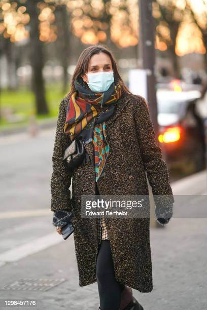 Guest wears a protective face mask, a colored long scarf, a brown glittering tweed long bronze colored coat, a black and white wool checked pullover...