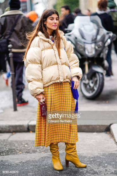 A guest wears a puffer coat a checked pattern skirt yellow boots during Paris Fashion Week Womenswear Fall/Winter 2018/2019 on March 1 2018 in Paris...