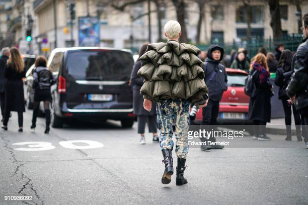 A guest wears a puffer khaki coat print pants black boots has tattoos and dyed hair outside Jean Paul Gaultier during Paris Fashion Week Haute...