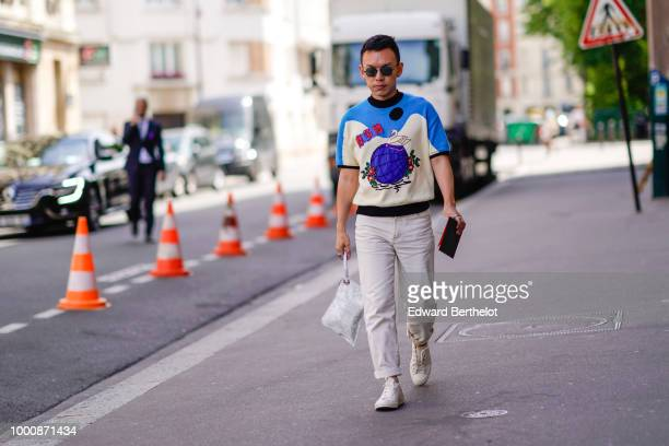 A guest wears a pullover with colored print white pants white shoes a white bag sunglasses outside Wooyoungmi during Paris Fashion Week Menswear...