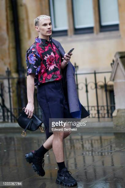 Guest wears a purple and red floral print shirt, dark blue shorts, a Dior black leather Saddle bag, sneakers, during London Fashion Week Fall Winter...