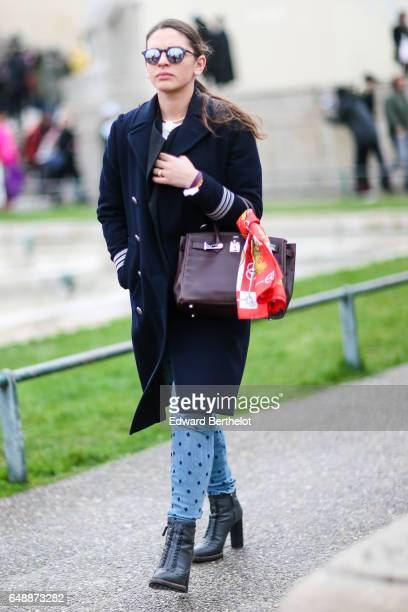 A guest wears a purple bag a blue coat blue pants and black boots outside the Hermes show during Paris Fashion Week Womenswear Fall/Winter 2017/2018...