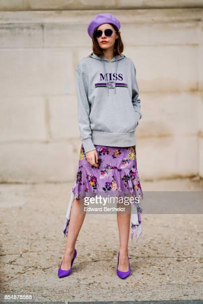 A guest wears a purple beret hat a gray hoodie a purple pleated skirt purple shoes sunglasses outside Margiela during Paris Fashion Week Womenswear...