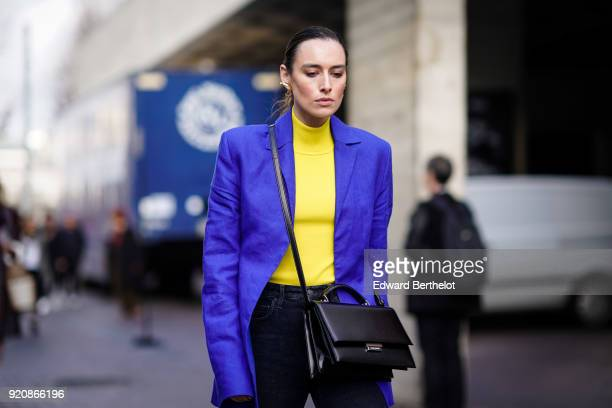 A guest wears a purple blazer jacket a yellow turtleneck a bag during London Fashion Week February 2018 on February 18 2018 in London England