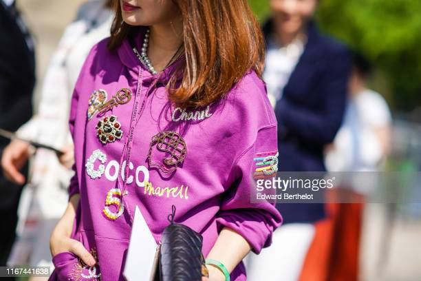 A guest wears a purple Chanel hooded sweatshirt with Chanel embroideries and brooches a black Chanel bag outside the Chanel Cruise Collection 2020 At...