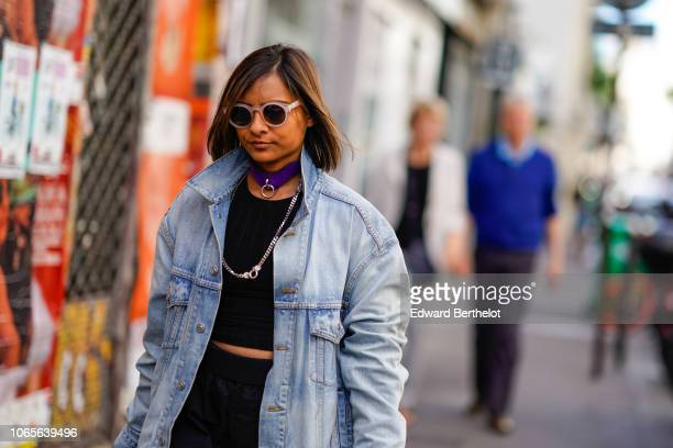 A guest wears a purple choker sunglasses a blue denim jacket a black top outside Yohji Yamamoto during Paris Fashion Week Menswear SpringSummer 2019...