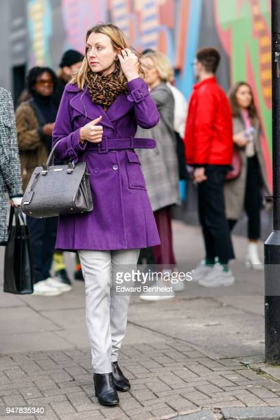 A guest wears a purple coat a bag white pants black shoes during London Fashion Week Men's January 2018 at on January 6 2018 in London England