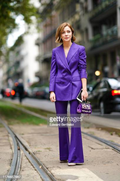 A guest wears a purple doublebreasted jacket purple flare pants nudecolor studded pointy heels a purple velvet handbag with floral embroideries...