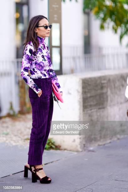 A guest wears a purple floral print turleneck top purple pants outside Haider Ackermann during Paris Fashion Week Womenswear Spring/Summer 2019 on...