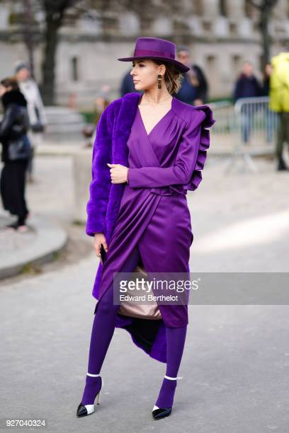 A guest wears a purple hat a purple dress during Paris Fashion Week Womenswear Fall/Winter 2018/2019 on March 3 2018 in Paris France