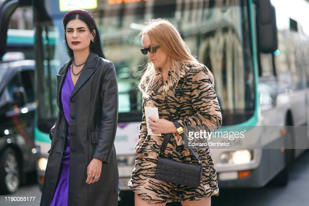 Guest wears a purple headband, a black leather long jacket, a purple dress, a necklace ; a guest wears sunglasses, a tiger print dress, a black...