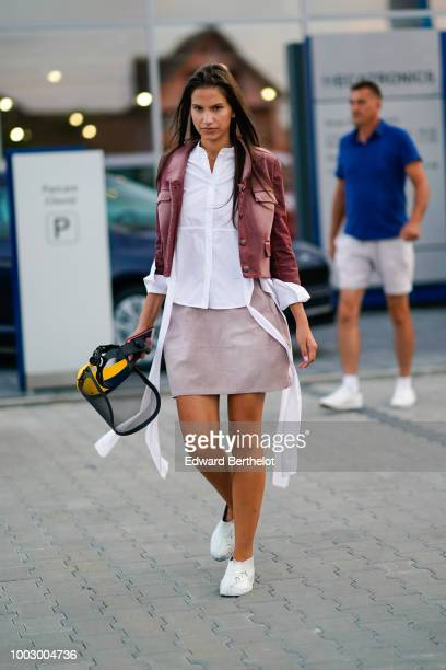A guest wears a purple jacket a white shirt a skirt white sneakers during Feeric Fashion Week 2018 on July 20 2018 in Sibiu Romania