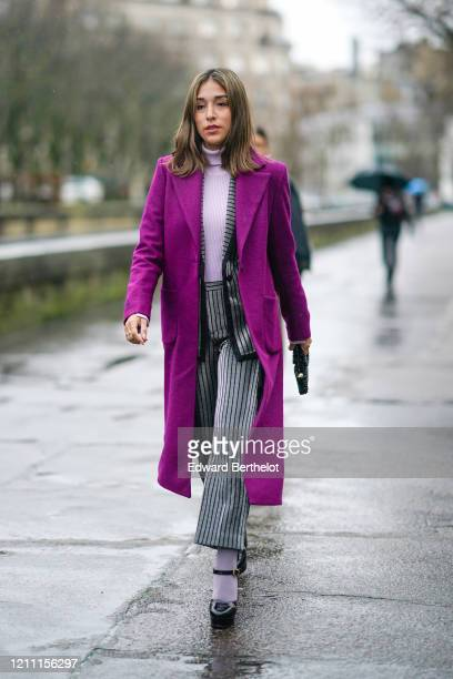 A guest wears a purple long coat a pale purple turtleneck pullover striped gray flared pants socks black leather shoes outside Valentino during Paris...