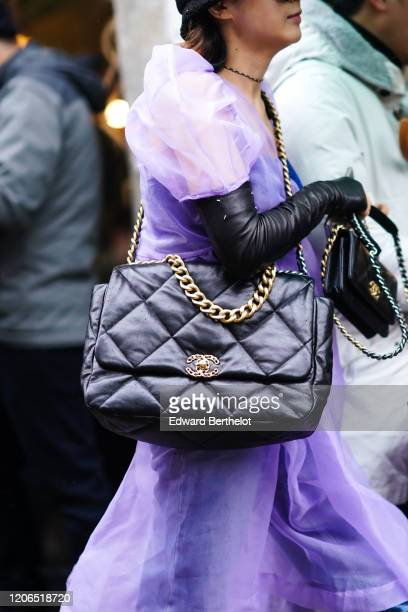 Guest wears a purple mesh flowing dress, black leather long gloves, a black leather quilted Chanel bag with a golden chain, during London Fashion...