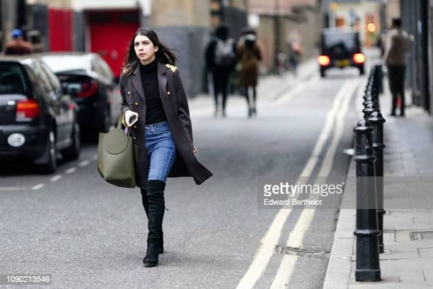 Guest wears a purple military coat with golden buttons and shoulder ornament, a green bag, black thigh high boots, during London Fashion Week Men's...