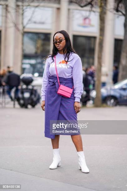 A guest wears a purple pull over sunglasses a purple skirt a pink bag white shoes outside Miu Miu during Paris Fashion Week Womenswear Fall/Winter...