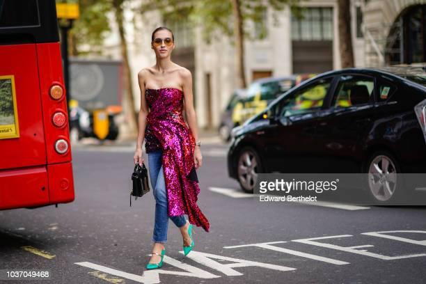 A guest wears a purple shiny glitter offshoulder dress blue denim jeans green shoes during London Fashion Week September 2018 on September 14 2018 in...