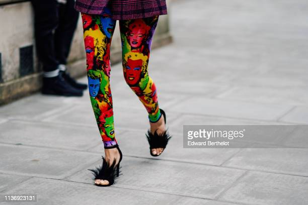 A guest wears a purple tartan jacket colorful skinny pants with printed images of Marylin Monroe and James Dean black feathers strappy heeled sandals...