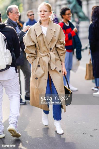 A guest wears a putty trench coat a black bag blue jeans white boots outside the Dries Van Noten show during Paris Fashion Week Womenswear...