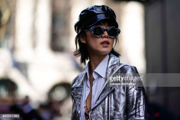 A guest wears a pvc black hat and sunglasses a silver shiny jacket during London Fashion Week February 2018 on February 16 2018 in London England