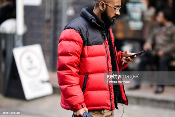 A guest wears a red and black puffer jacket from The North Face earphones during London Fashion Week Men's January 2019 on January 05 2019 in London...