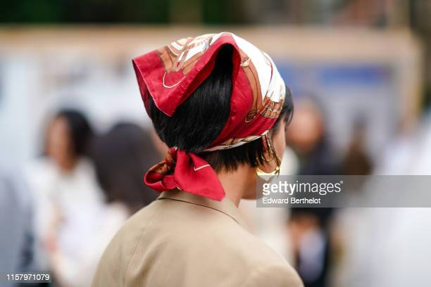 A guest wears a red and brown hair scarf earrings a beige jacket outside Hermes during Paris Fashion Week Menswear Spring/Summer 2020 on June 22 2019...